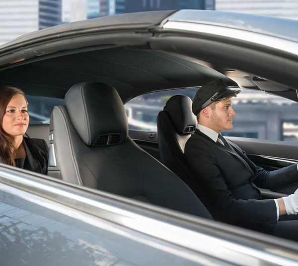 61135128 - beautiful young woman traveling in a car with male handsome chauffeur